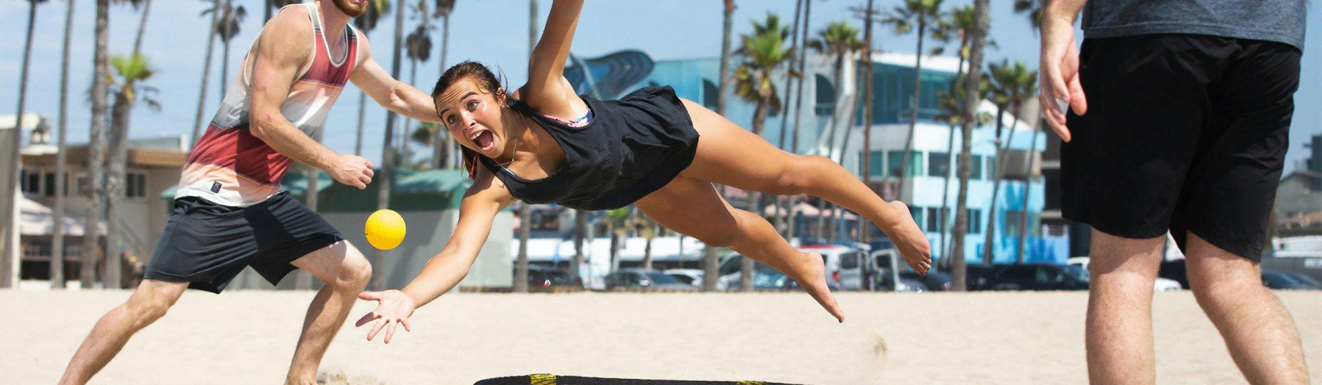 Personen spielen Spikeball am Strand