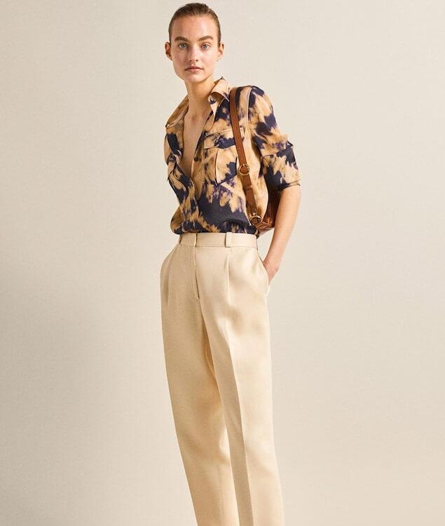 Modelka v tmavě modrobéžové batikované košily a béžových kalhotách.