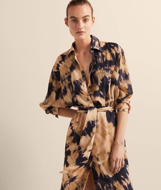 Modelka v tmavě modrobéžových batikovaných zavinovacích šatech.