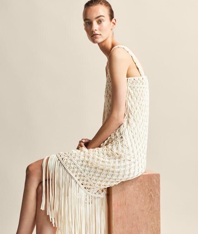 Modelka v bílých háčkovaných šatech.