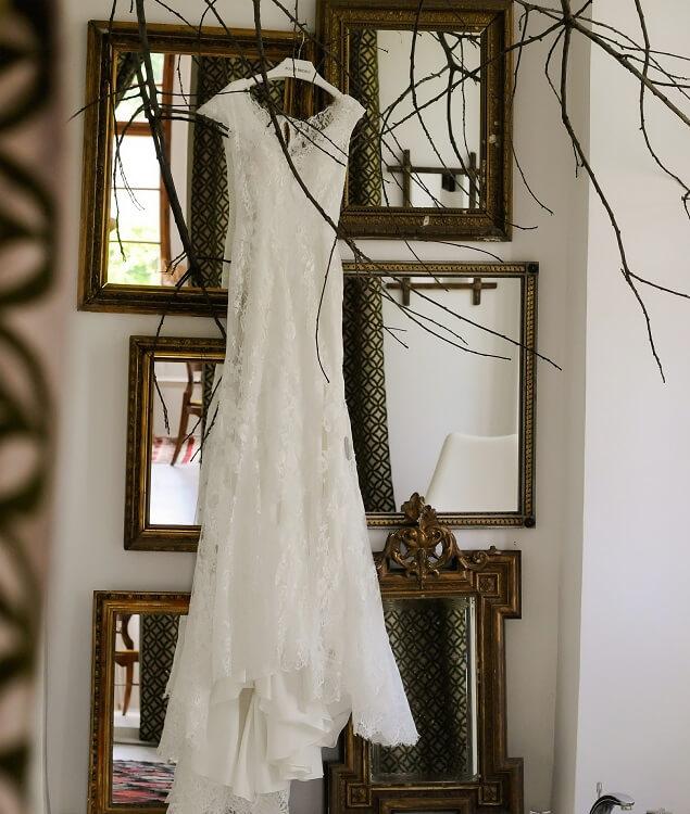 Bílé svatební šaty visící na ramínku.
