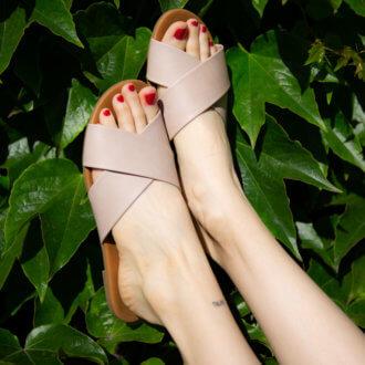 Nohy obuté v růžových pantoflích od Deichmannu.