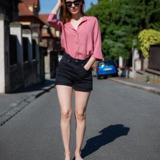 Modelka oblečená v růžové halence, černých krátkých kraťasech a obutá v růžových pantoflích.