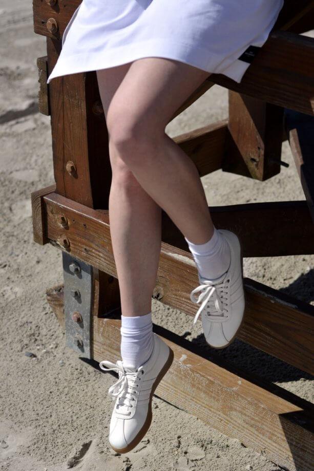 Weiße Sneaker am Strand