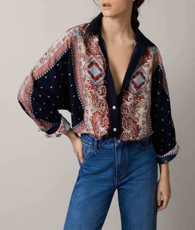 Modelka v tmavej blúzke a džínsoch.