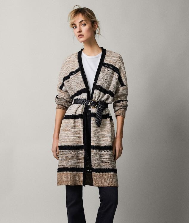 Modelka oblečená v dlhom pletenom svetri nad kolená, ktorý je v páse stiahnutý opaskom.