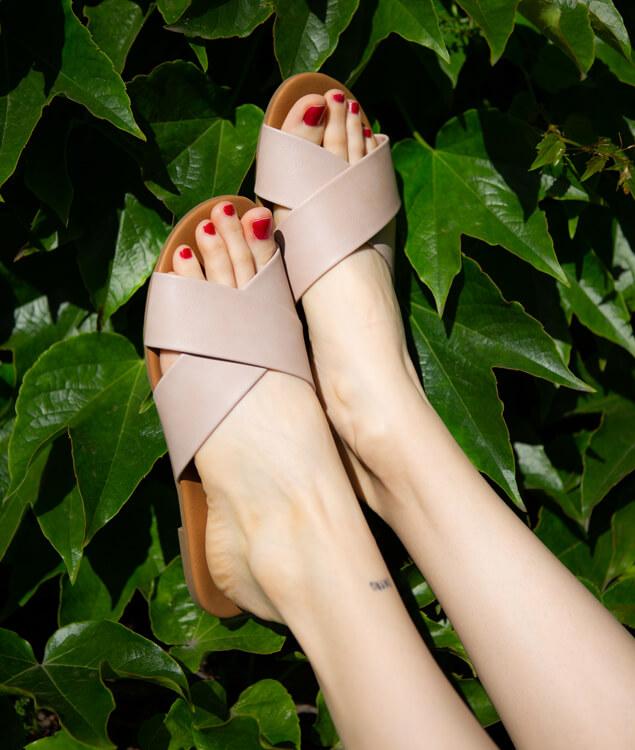 Nohy obuté v ružových šľapkách.