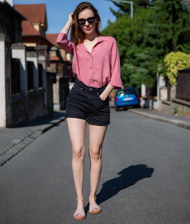 Modelka oblečená v ružovej blúzke, čiernych krátkych kraťasoch a obutá v ružových šľapkách.